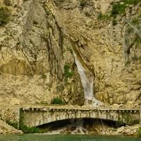 Ein wunderschön anmutendes Bild mit einem Wasserfall hinter einem stillgelegten Tunnelsystem.